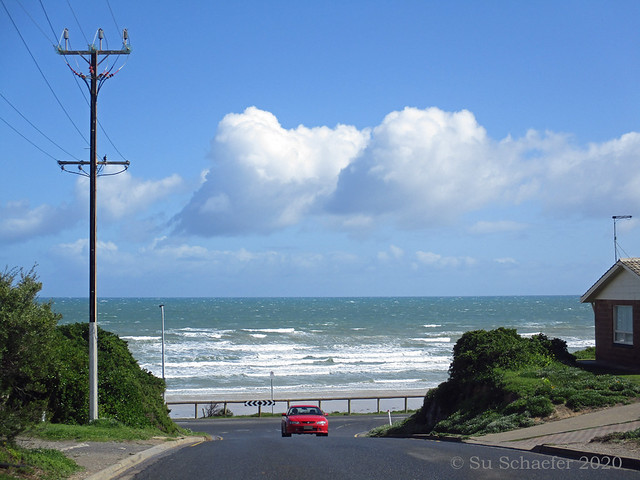 Stormy sea with red car