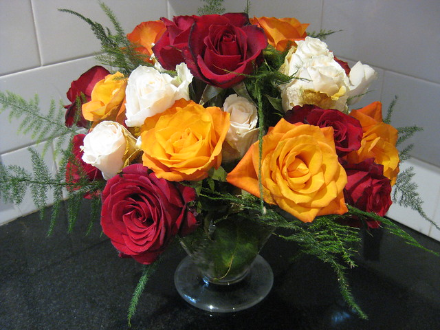 Christmas Centrepiece of Fiery Orange, Red and Cream Roses