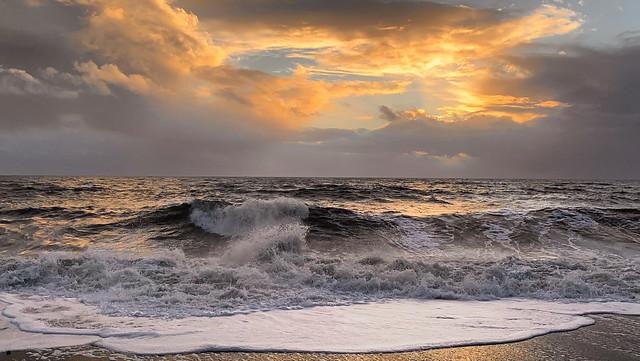 Setting sun and heavy seas at Hive Beach, Burton Bradstock, Dorset