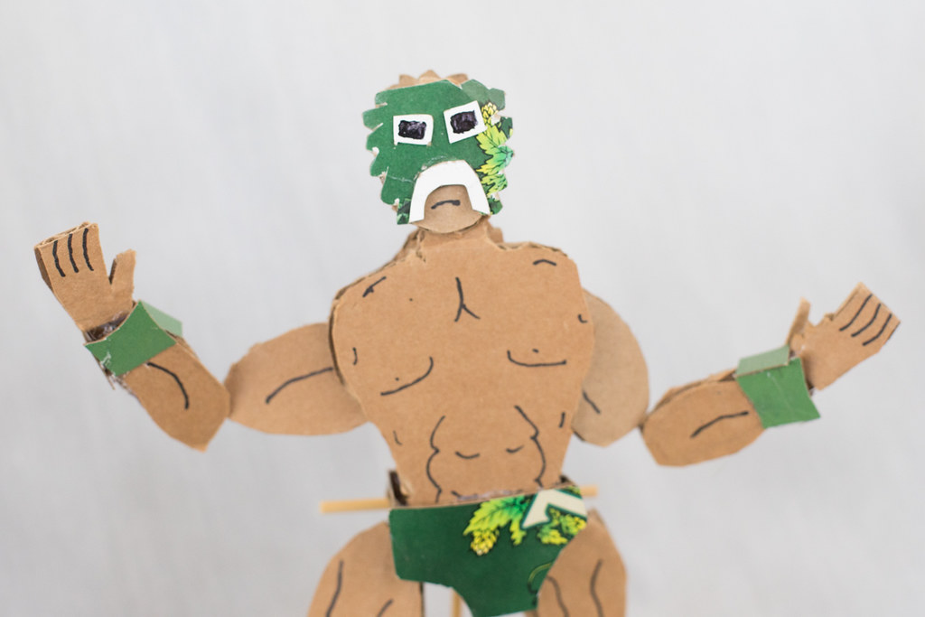 Sculpture of luchador made from cardboard featuring a green mask and evocations of a tree