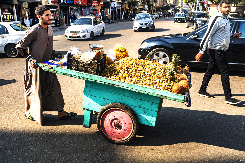 Man pushing cart of pistachios, pineapples and coconuts near El Gomhoreah Square on 12-30-20--Cairo