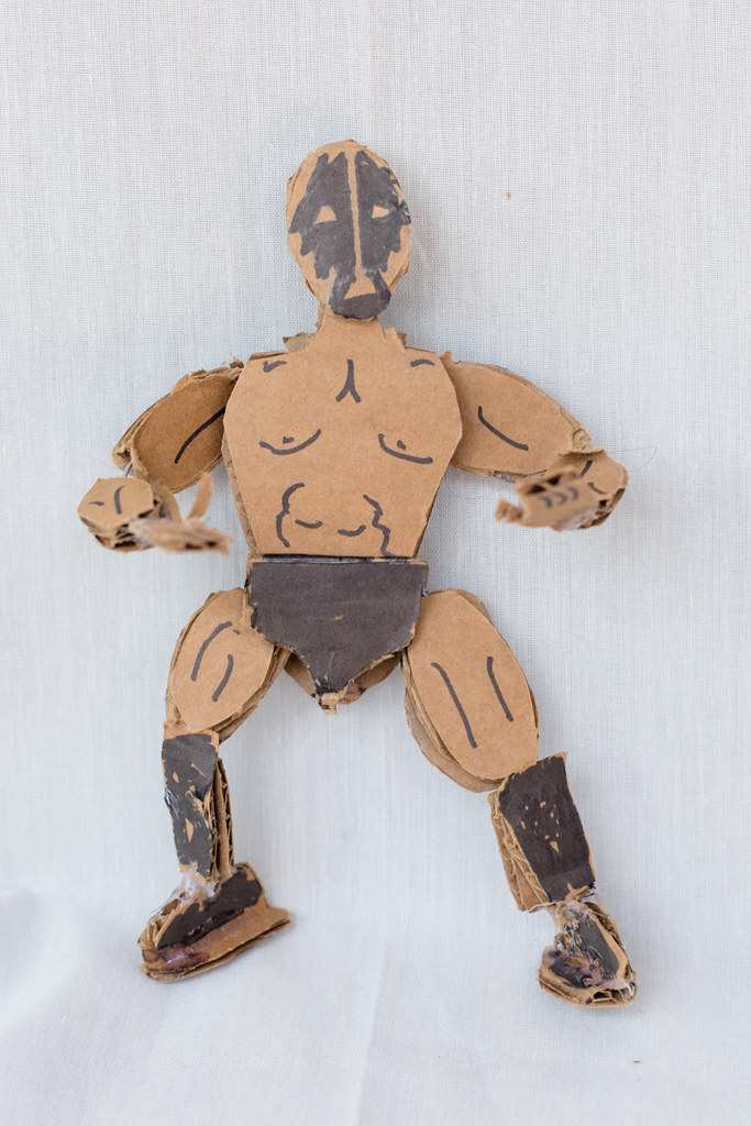 Sculpture of a man made of wire and cardboard shapes, made to look like a masked wrestler with ink marker