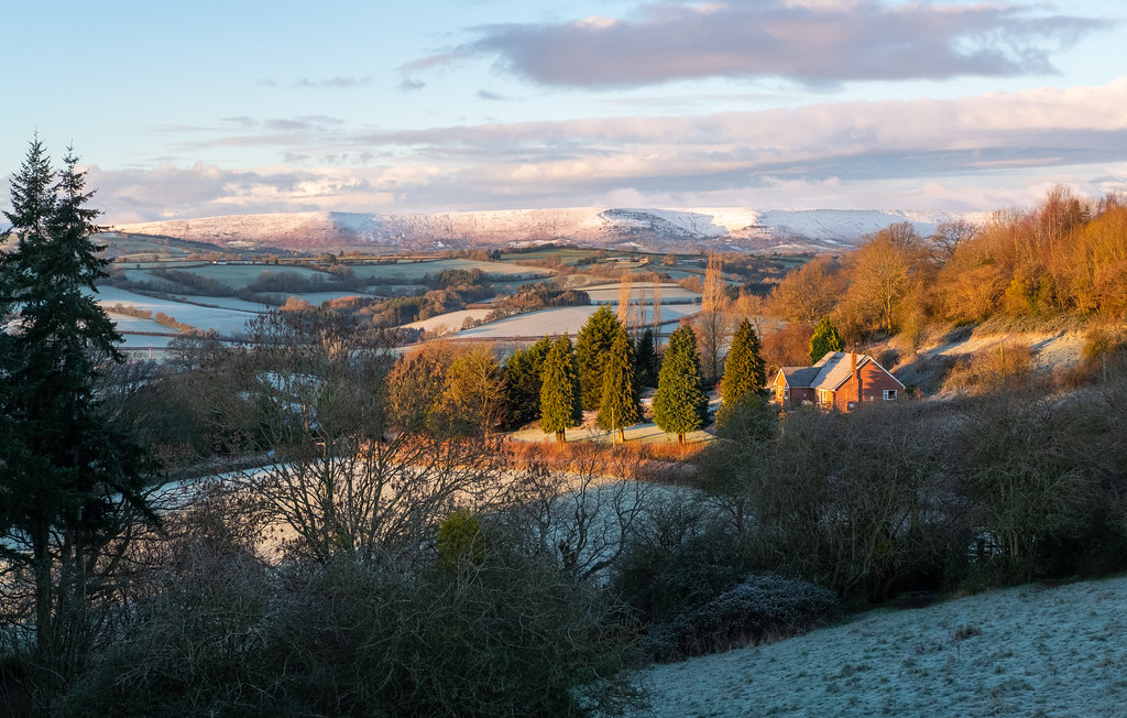 Photo of a view over a valley of fields lit by sunrise with a snowy ridge forming the horizon and a red brick house to one side looking over it all
