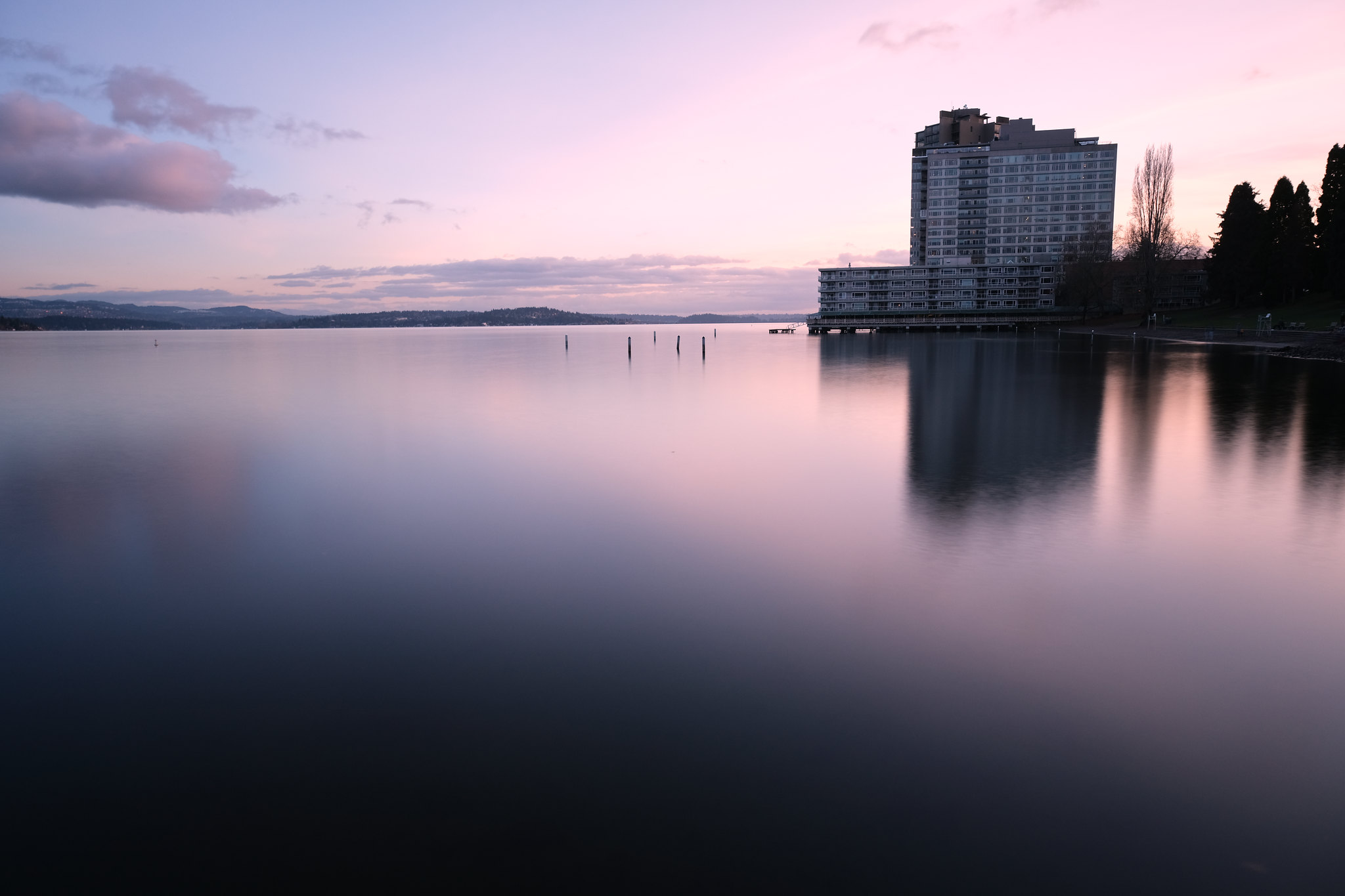 Seattle, WA, US - Long exposure photograph of some buildings on Lake Washington. The sky is pink, and the water looks almost still because of the long exposure effect.