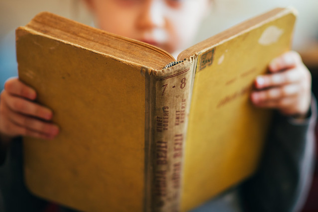 Little girl holding old book closeup.