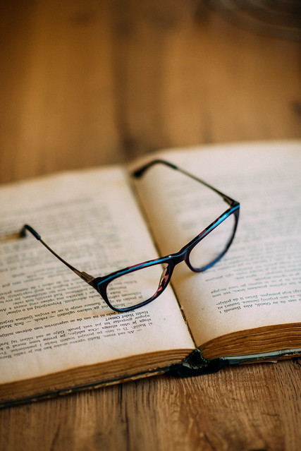 Glasses and old book on wooden table closeup.