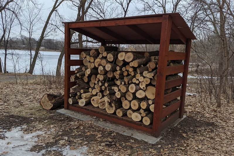 A small wooden shelter nearly filled with logs.