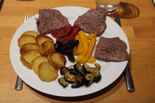Kurz angebratenes Rindfleisch mit Kartoffelchips, Zucchinigemüse, getrockneten Tomaten, schwarzen Oliven und karamellisierten Paprikastreifen