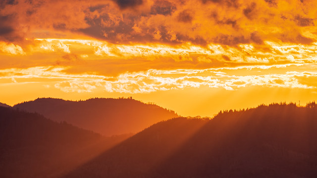 The sun shines over a mountain ridge in the northern black forest