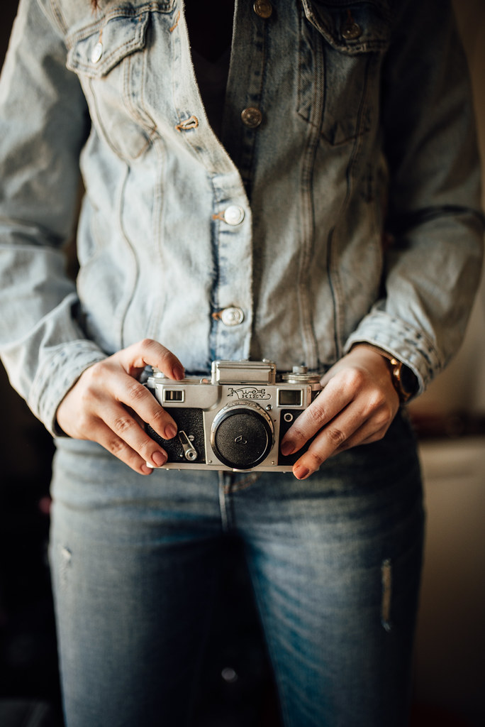 Young woman hand holding an old film camera.