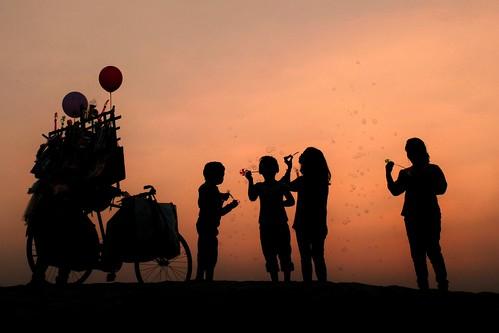 sunset silhouette children balloon bubbles joy villagelife riverbed damodar bengal india