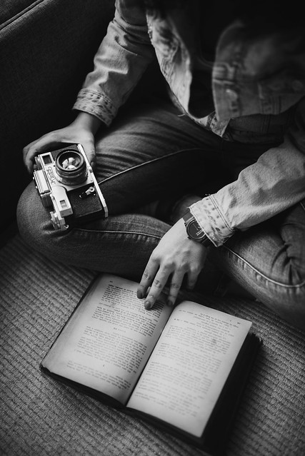 Woman in denim jacket holding analog camera and reading a book.
