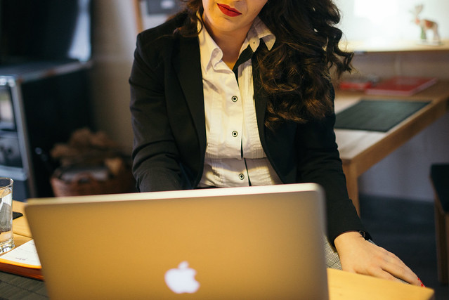Businesswoman with beautiful lips working on her laptop closeup.