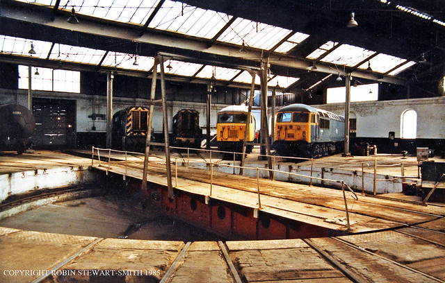 BR Class 56 Nos 56120 and 56002 together with Class 08 Nos 08340 and 08141 inside Barrow Hill Diesel Depot Roundhouse (MR) on 25th August 1985