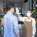restaurant staff checking scan fever by digital thermometer to customer for protect infection coronavirus