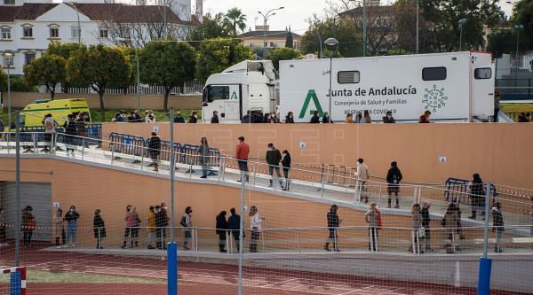 Un grupo de docentes y trabajadores de centros educativos hace cola para hacerse un test en la localidad sevillana de Tomares. EFE - Archivo