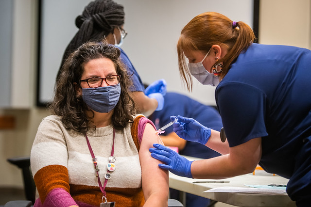 Auburn employee Amy Wiley is given the COVID-19 vaccination by a healthcare worker