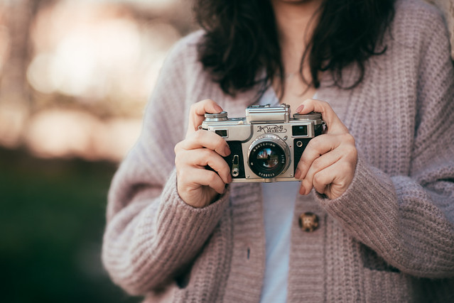 Woman using an old film camera outdoors.