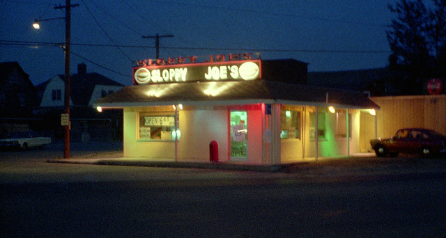 Sloppy Joe's restaurant glows at twilight in multiple colors on a hot and humid night. At the intersection of Merwin and Seabreeze Avenues directly on the Long Island Sound shoreline, this was a great burger and hot dog joint! Milford CT. July 1973