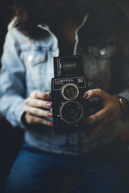 A girl in a denim jacket holds an analog camera in her hands.