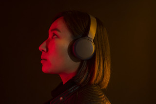 Asian woman listening to music with wireless headphones | by TwinPeaks99
