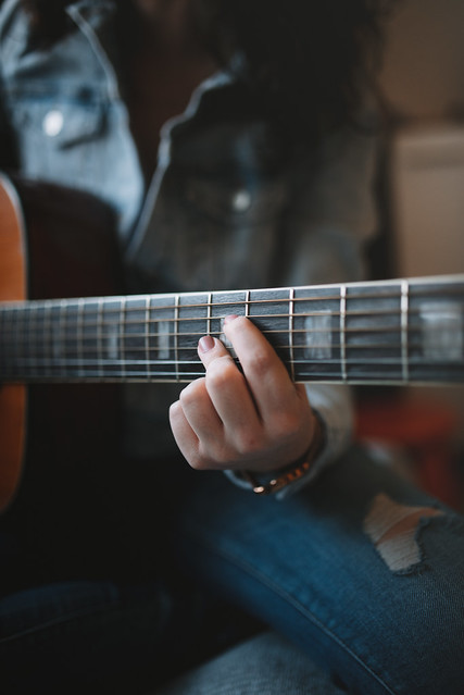 Wrong chord with two fingers on accoustic guitar closeup.