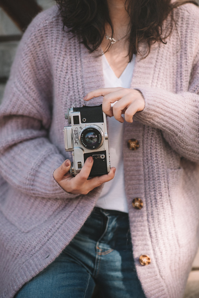 Young woman photographs with an analog camera.