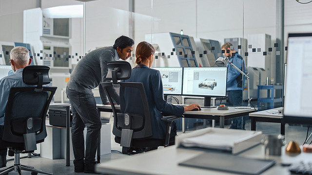 Automotive Design Factory: Project Manager and Chief Mechanical Engineer Talk, Point at Computer Display Showing 3D Electric Car Model in CAD Software. High Tech Facility with Automatic CNC Machinery