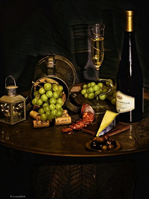 Bodegón, vino blanco, queso, uvas, salchicha picante y olivas