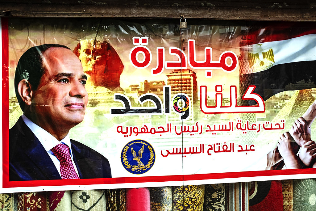 Al-Sisi with Sphinx in background in window of carpet store on 1-9-21--Cairo
