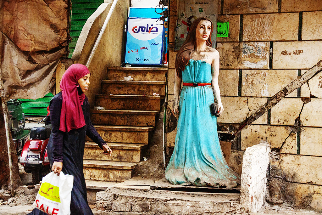 Woman walking by statue of woman on Bab El-Wazir on 1-9-21--Cairo