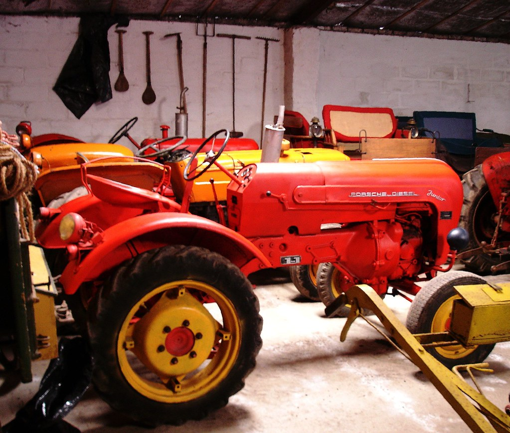 ... and between ropes, seed drills, shovels and tarpaulins a red - and yellow - Porsche Tractor ...