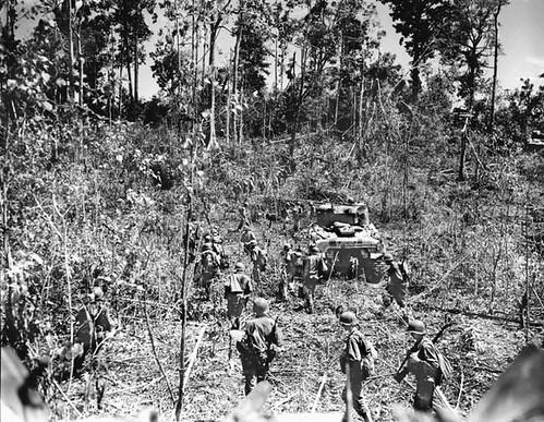 Amerikaanse troepen en ondersteunende Sherman tanks rukken op door het oerwoud bij het vliegveld Mokmer.