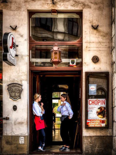 Two young ladies at a doorway to an espresso shop in the main square (Rynek Główny) of the Old Town of Kraków where the Grodzka Street begins, Poland. 647-Edita