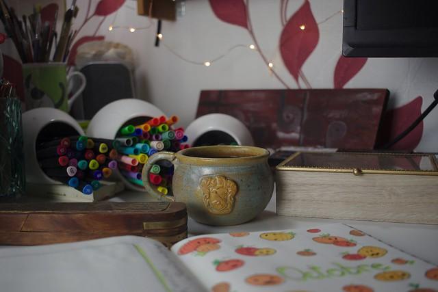 Bullet journal ouvert sur un bureau, avec tasse de thé artisanale