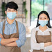 Asian barista putting on safety mask working in cafe after reopening during pandemic