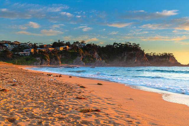 Sunrise at the Beach with light cloud and headland with houses