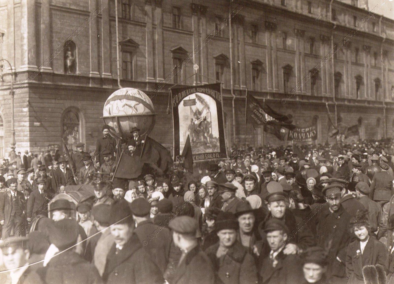 1919. Колонна демонстрантов со знаменами, транспарантами на городской улице во время празднования 1-го Мая