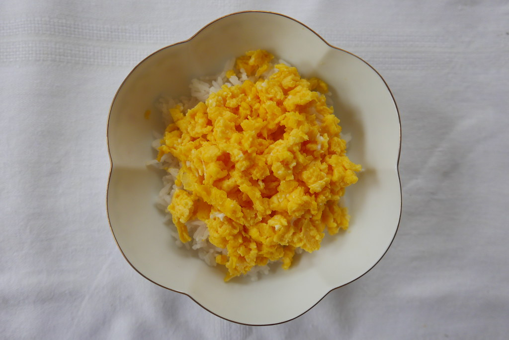 Scrambled eggs in a bowl over rice.