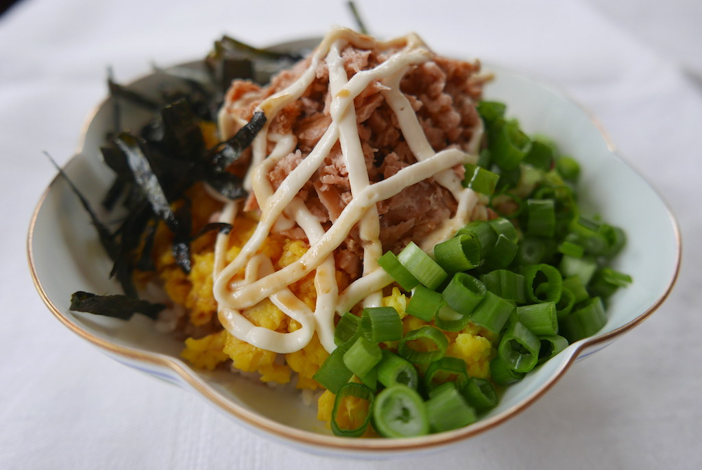 A sideways look of the rice bowl including seaweed, green onion, mayo, brown sauce, egg, tuna, and rice.