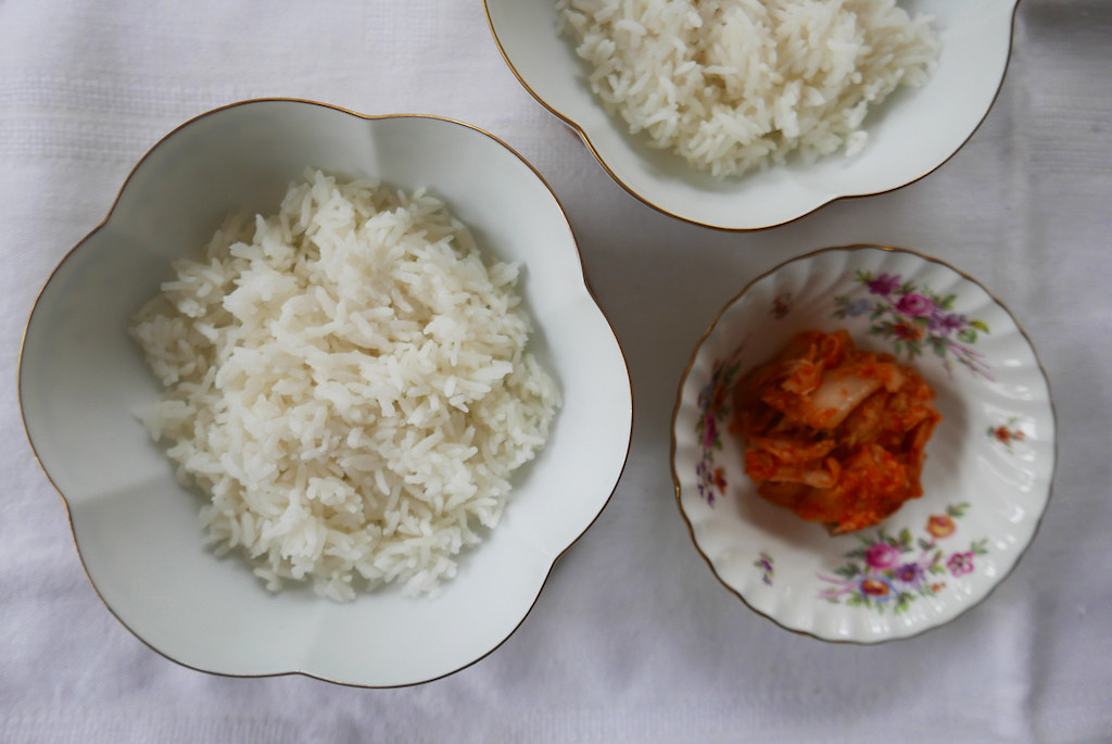 Rice in bowls next to a bowl of kimchi.