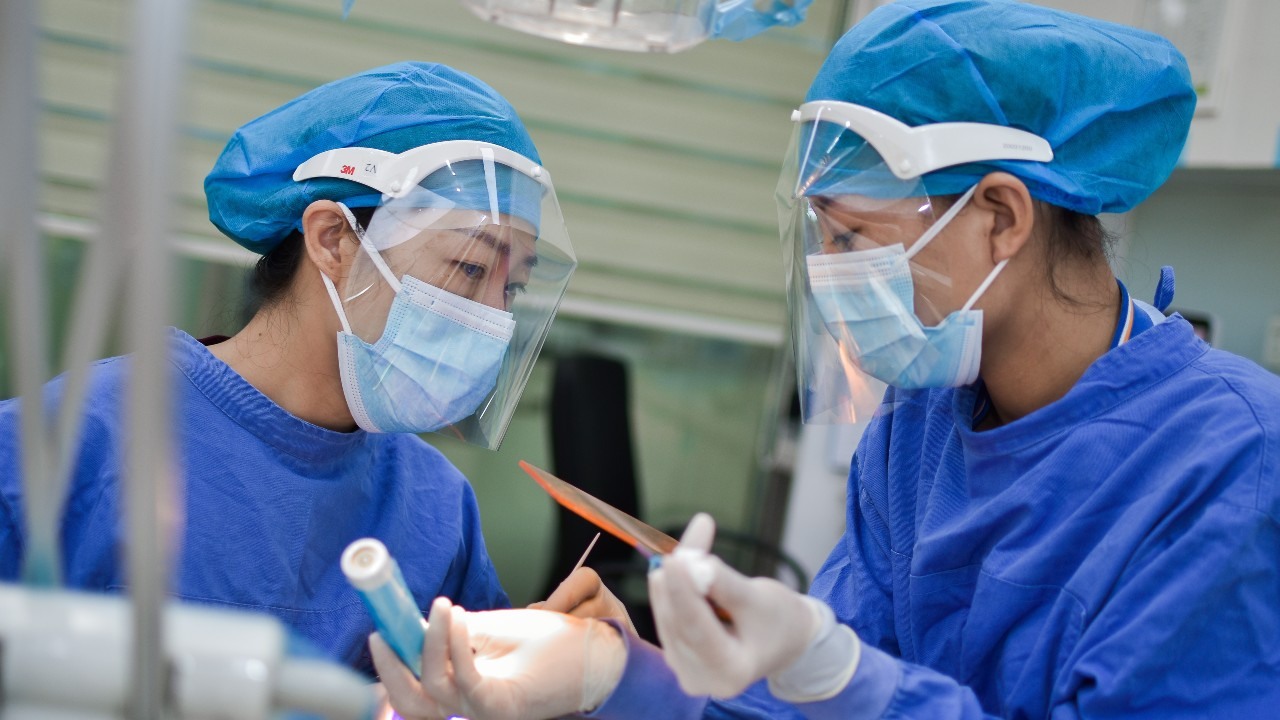 Doctors in PPE treating a patient