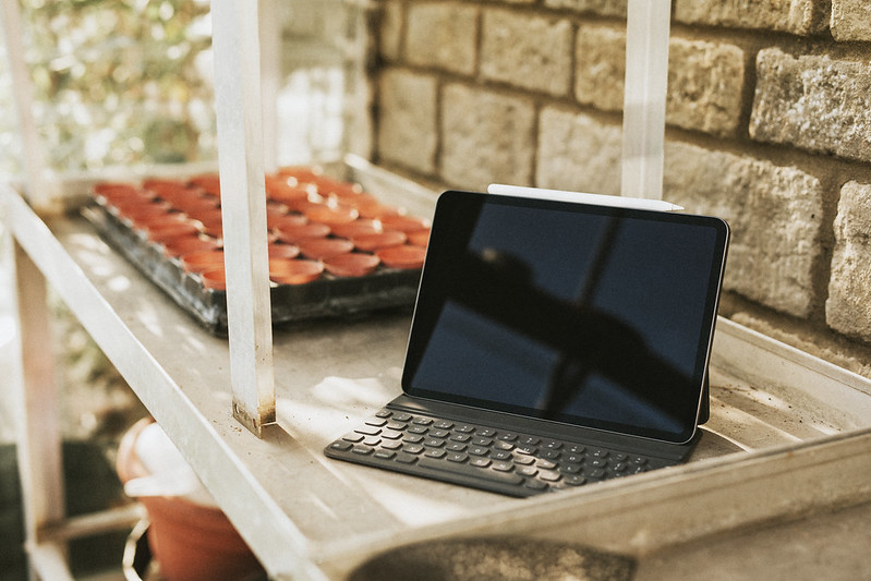 Black tablet with keyboard on a gardening wooden table