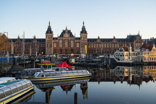 Amsterdam, Netherlands - November 9, 2019: House boats and tourist boats along Signel canal during an early autumn fall morning outside of Amsterdam Centraal train station