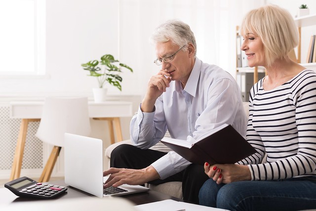 Elderly Couple Checking Their Bills On Laptop At Home