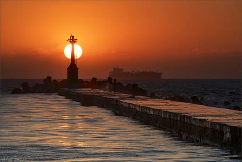 portofkaohsiung dusk seascape wave ocean shore seaside coast landscape outdoor clouds sky water goldensunset lighthouse cargoship