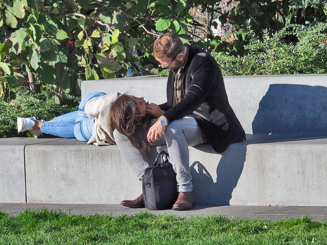 Girl lying on a bench with her head on her boyfriend's lap