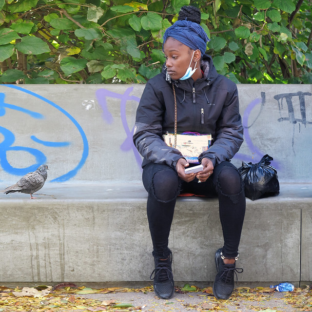 Muslim girl sitting and intrigued by a pigeon