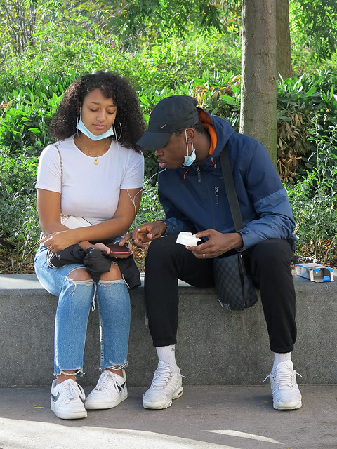 Black guy checking the contents of his girlfriend's smartphone