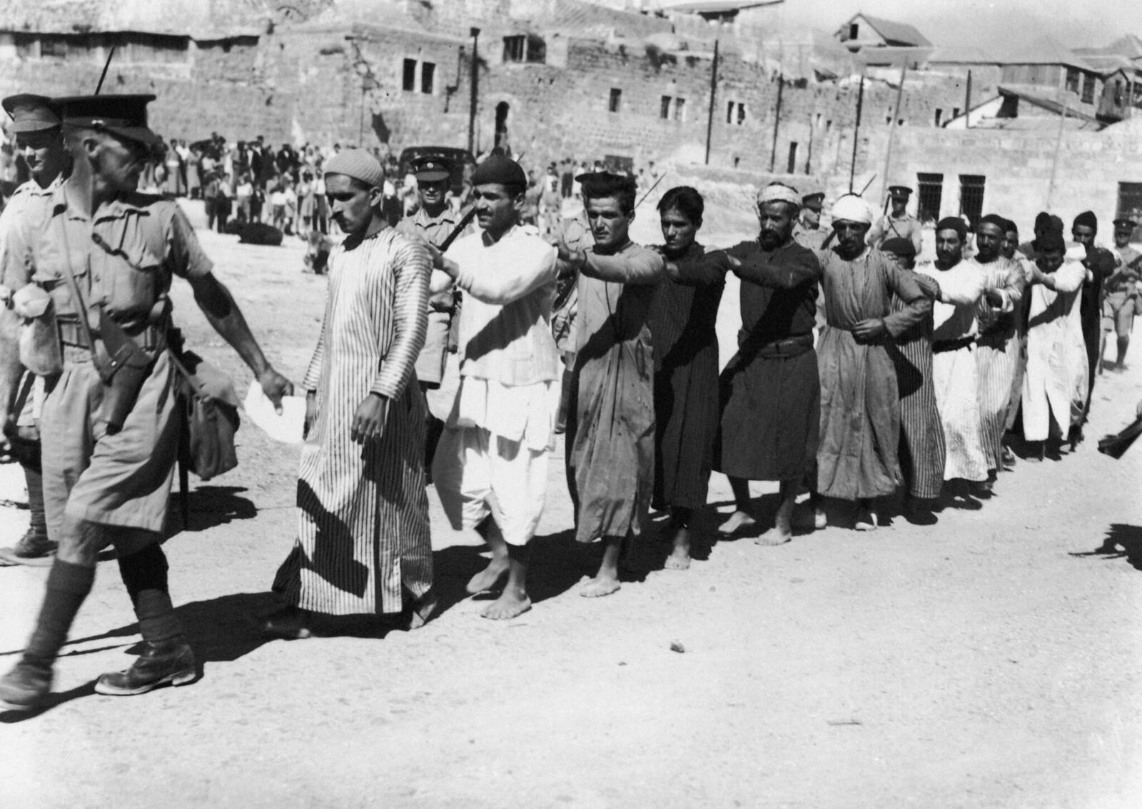 13. 1938. Британские солдаты сопровождают группу арабских заключенных из Старого города Иерусалима. 26 октября